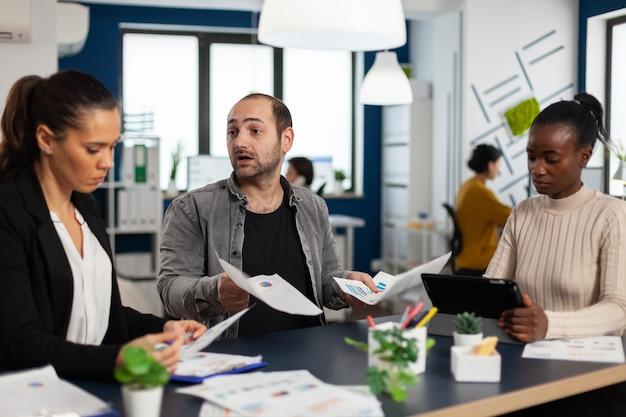 Besorgtes startup-team, das über finanzielle ergebnisse diskutiert, am schreibtisch im büro sitzt und die nächste strategie für die suche nach tablet-lösungen plant. multiethnische geschäftsleute arbeiten