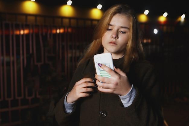 Besorgtes teenager-mädchen, das ihr smartphone in einem park mit unscharfem hintergrund anschaut