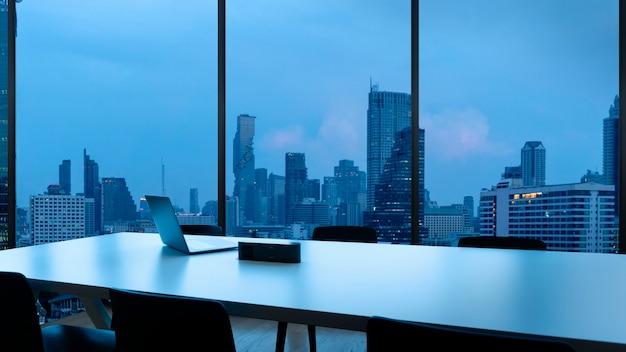 Besprechungsraum und arbeitsplatz mit notebook laptop bequeme arbeitstisch in bürofenstern und bangkok blick auf die stadt.