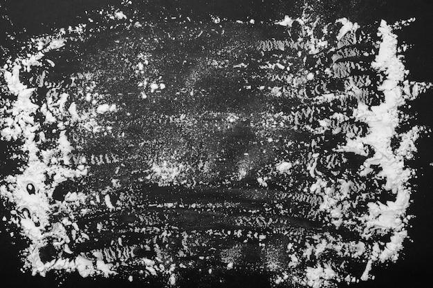 Besprühen sie weizenmehl auf dunklem schwarzholzhintergrund