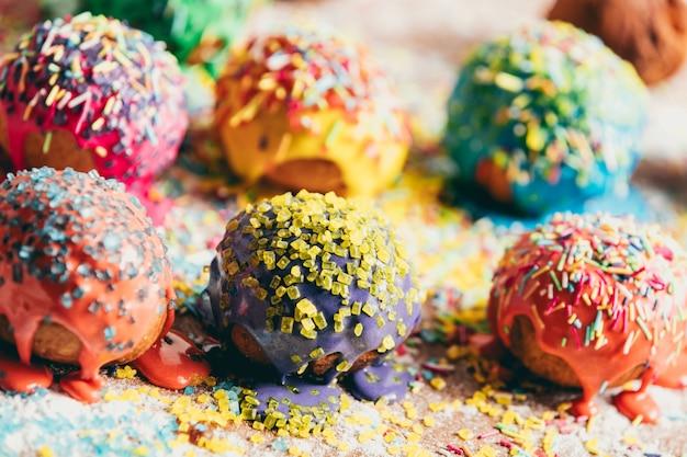 Besprühte donuts, die auf einen unordentlichen zähler legen