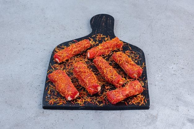 Besprühte süßigkeitenbeschichtung auf türkischen köstlichkeiten auf einem brett, auf marmorhintergrund.
