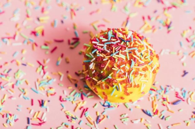 Besprühter gelber donut auf rosa hintergrund.