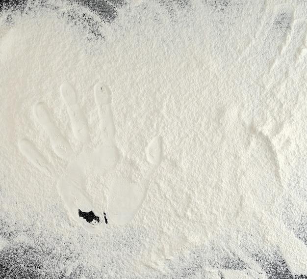 Besprühtes weißes weizenmehl auf einer schwarzen tabelle