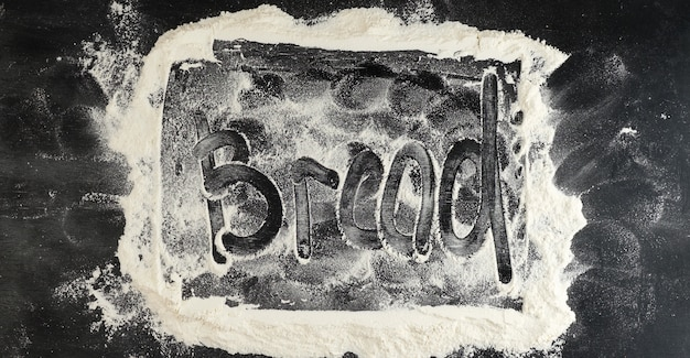 Besprühtes weißmehl auf einem schwarzen tisch und brot-aufschrift auf der oberfläche