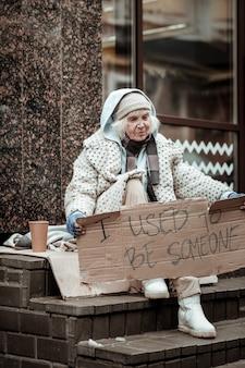 Bessere zeiten. unglückliche traurige frau, die an ihre vergangenheit denkt, während sie arm und obdachlos ist