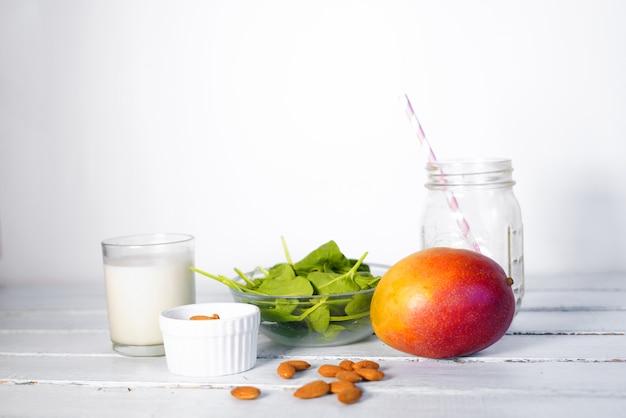 Bestandteile des gesunden green reach vitamins smoothie mit baby-blattspinat, mango, mandelmilch und erdbeere