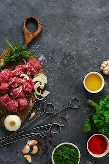 Bestandteile für das kochen des fleisches mit gemüse auf einer draufsicht des dunklen hintergrundes. vorbereitung rindfleisch