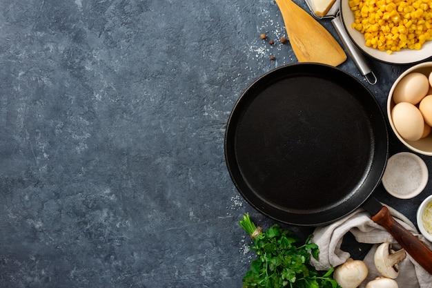 Bestandteile für das kochen von gesunden frühstückseiern mit leerer kochender wanne und pilzen, mais, eiern, spinat und käse auf dunklem steinhintergrund