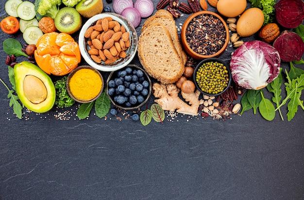 Bestandteile für die gesunde nahrungsmittelauswahl gründeten auf dunklem steinhintergrund.