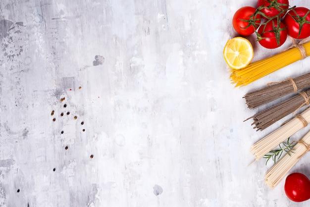 Bestandteile für die zubereitung der teigwaren und der soße lokalisiert auf steinhintergrund.