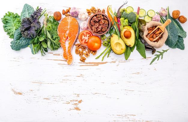Bestandteile für gesunde nahrungsmittelauswahl auf weißem hölzernem hintergrund.