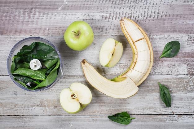 Bestandteile für grünen smoothie mit äpfeln, spinat und banane auf hölzerner hintergrundtabelle. draufsicht