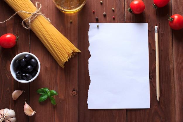 Bestandteile für italienische teigwaren auf holztisch mit papier für das schreiben von rezepten.