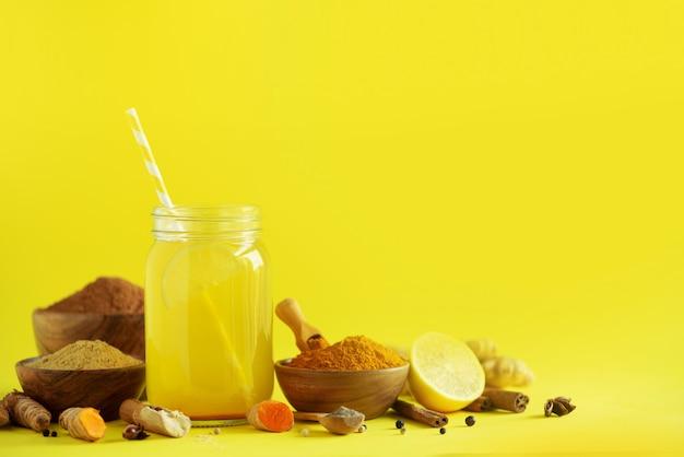 Bestandteile für orange gelbwurzgetränk auf gelbem hintergrund. zitronenwasser mit ingwer, kurkuma, schwarzem pfeffer. veganes heißes getränkkonzept