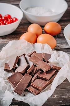 Bestandteile für schokoladenkuchen brauni auf schwarzem hölzernem hintergrund