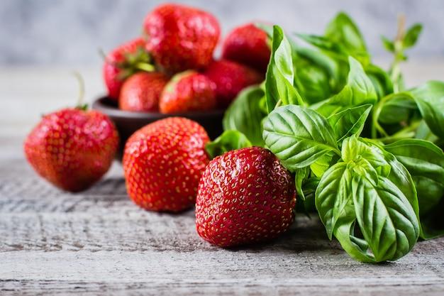 Bestandteile für sommer-getränk-erdbeer-basilikum-limonade auf konkretem tabellenhintergrund. nahansicht