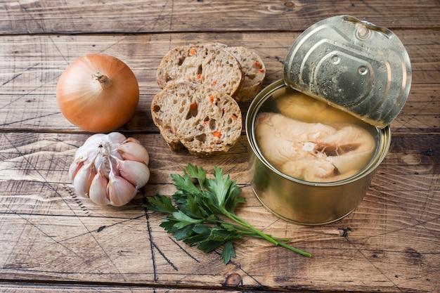 Bestandteile für suppenglas mit rosa lachsfisch, stücken brot, zwiebel und knoblauch mit grüns auf holztisch.