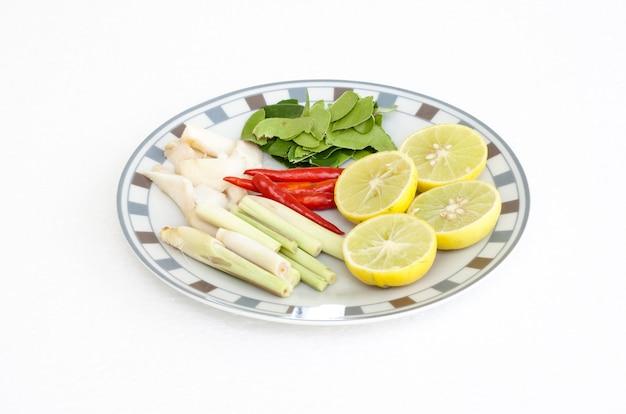 Bestandteile für thailändische küche im teller (zitronengras, pfeffer, zitrone, limettenblätter) auf weißem hintergrund
