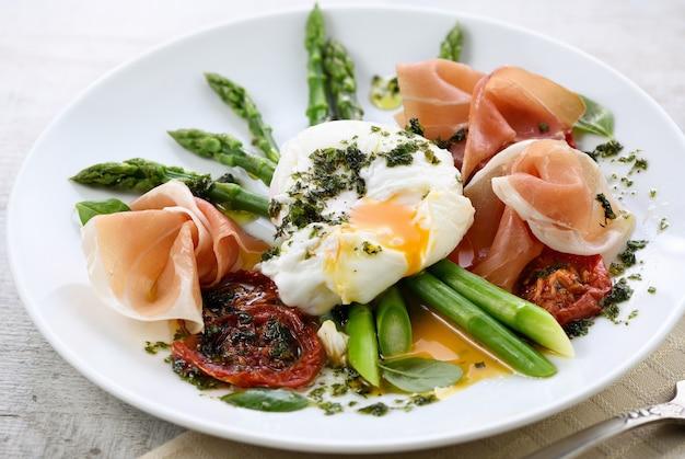 Beste eier benedict - pochierte eier mit schinken, spargel, sonnengetrockneten tomaten und pesto