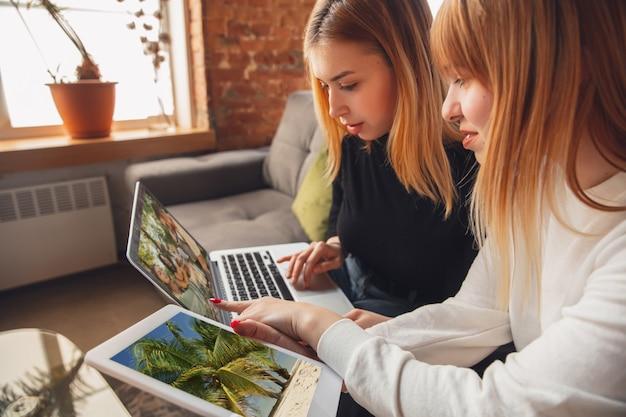Beste erinnerungen. junge freunde, frauen, die mit gadgets kino, fotos, online-kurse, selfies oder vlogs anschauen. zwei kaukasische weibliche modelle zu hause, die spaß haben und laptop, tablet, smartphone verwenden.
