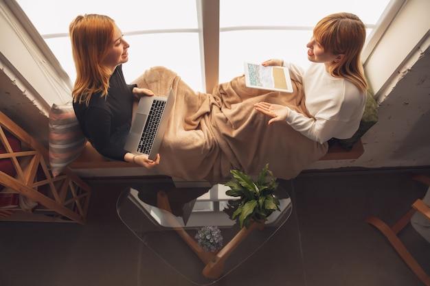 Beste erinnerungen. junge freunde, frauen, die mit gadgets kino, fotos, online-kurse, selfies oder vlogs anschauen. zwei kaukasische weibliche modelle zu hause in der nähe des fensters mit laptop, tablet, smartphone.