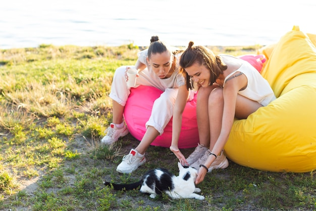 Beste freunde auf sitzsäcken, die mit einer katze spielen