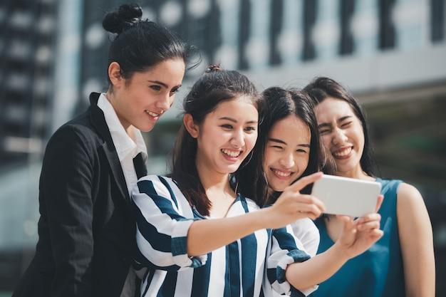 Beste freunde der asiatischen lebensstilgeschäftsfrau, die gehendes selfie des spaßes an der stadt lächeln und haben
