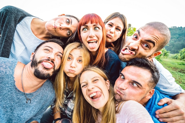 Beste freunde, die ein lustiges selfie bei einem picknickausflug machen, der die zunge herausstreckt - jugendlebensstilkonzept mit jungen leuten, die gemeinsam spaß im freien haben - warmer heller filter mit fokus auf zentralen gesichtern