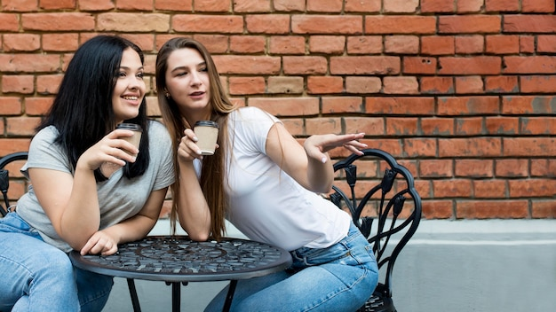Beste freunde, die ihren kaffee zusammen mit kopierraum nehmen