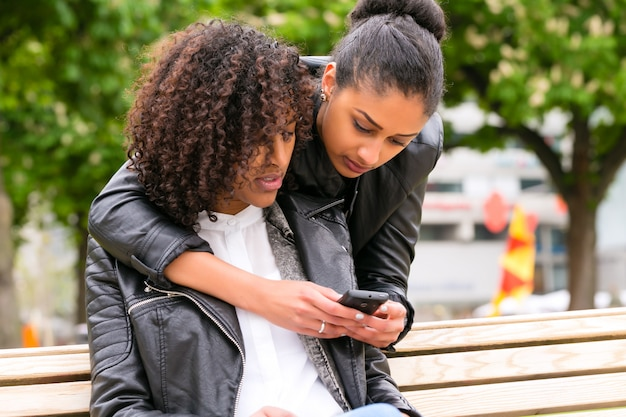 Beste freunde, die mit smartphone auf parkbank plaudern