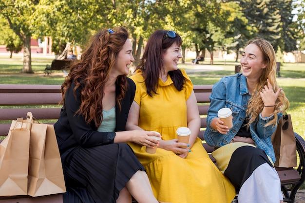 Beste freunde, die sich unterhalten, während sie auf einer bank sitzen