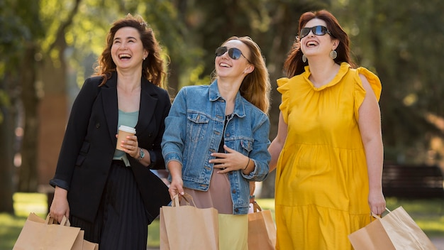Beste freunde, die sich unterhalten, während sie mit einkaufstüten im park spazieren gehen