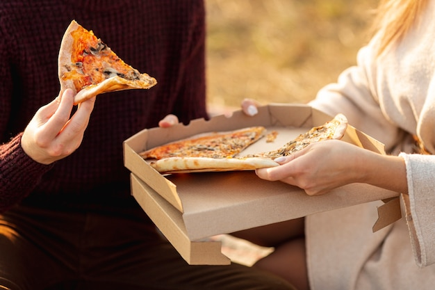 Beste freunde, die zusammen eine pizza außerhalb der nahaufnahme genießen
