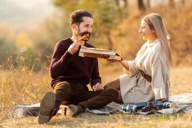 Beste freunde, die zusammen eine pizza draußen genießen