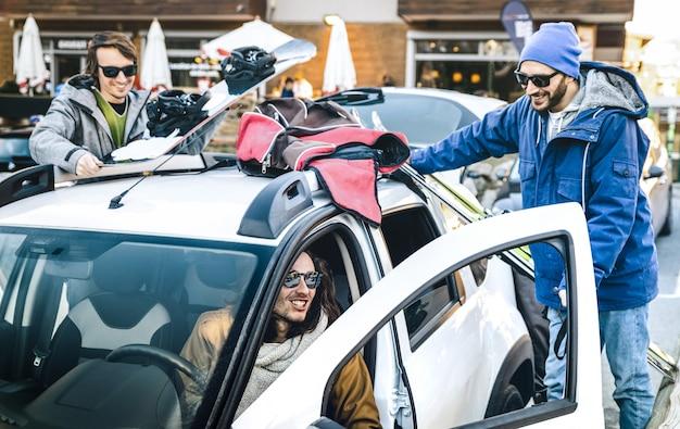 Beste freunde, die zusammen spaß haben und auto für ski und snowboard an der gebirgsreise vorbereiten