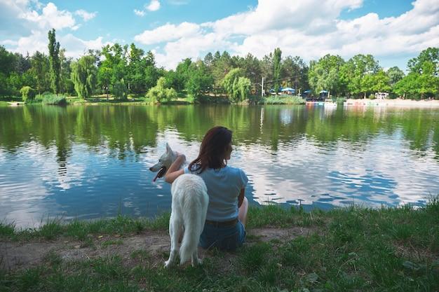 Beste freunde, frau, die einen hund umarmt, sich ausruht, während sie den atemberaubenden blick auf landschaft, see genießt, der himmel und bäume reflektiert. rückansicht.