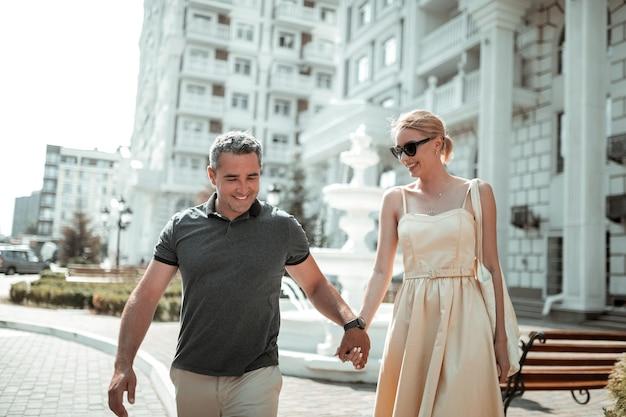 Beste freunde. fröhlicher ehemann und ehefrau sprechen und halten händchen während ihres spaziergangs an einem sonnigen sommertag.
