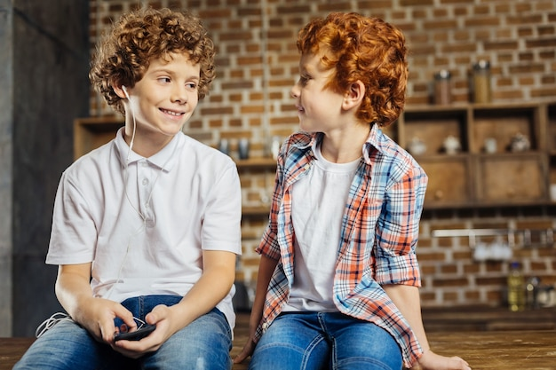 Beste freunde für immer. chestnut lüftete einen jungen, der seinen kleinen bruder mit einem fröhlichen lächeln im gesicht ansah, während er zu hause plauderte und auf einer kücheninsel saß.