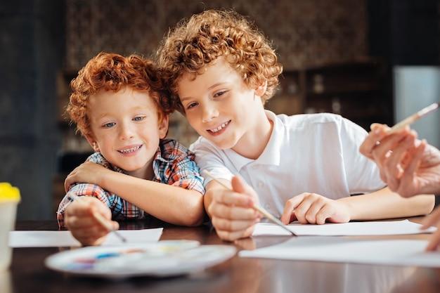 Beste freunde für immer. porträt von zwei fröhlichen lockigen stören, die breit grinsen, sich aneinander lehnen und den malprozess genießen, während sie an einem tisch sitzen.