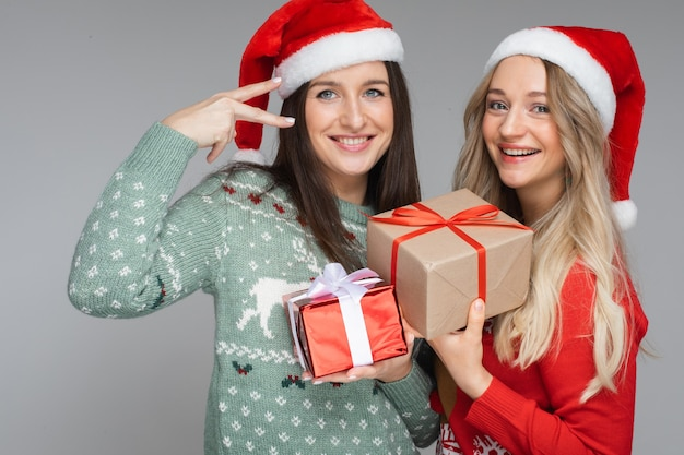 Beste freunde in weihnachtsmützen mit weihnachtsgeschenken.