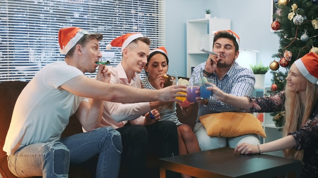 Beste freunde machen jubel und blasen party pfeifen auf weihnachtsfeier