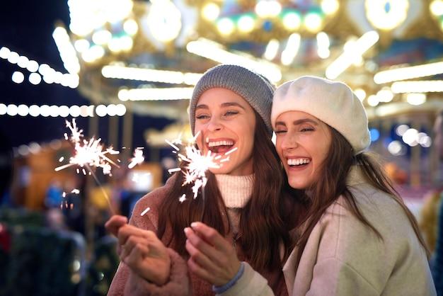 Beste freunde mit wunderkerzen auf dem weihnachtsmarkt
