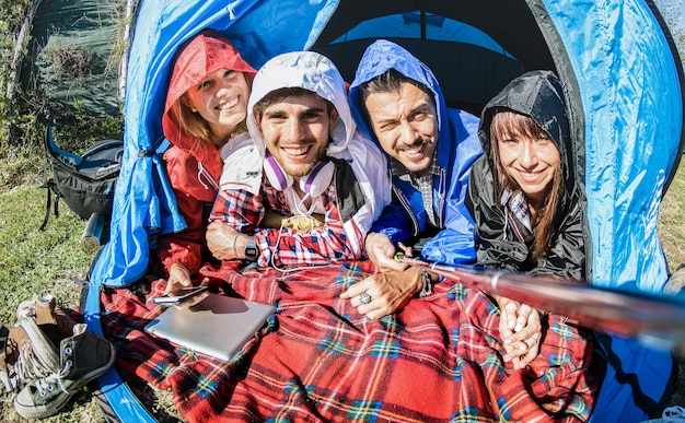 Beste freunde paare, die selfie im campingzelt am sonnigen tag nach dem regen nehmen
