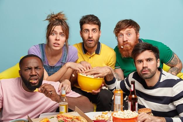 Beste freunde schauen sich gemeinsam einen spektakulären film an, essen popcorn, sind überrascht auf dem bildschirm, drücken großes staunen aus, trinken kaltes bier oder ein energiegeladenes getränk, genießen fast food. freundschaft, freizeitkonzept