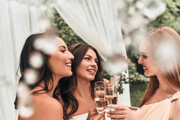 Beste freunde sind immer dabei. attraktive junge braut, die mit ihren schönen brautjungfern mit champagner anstößt, während sie zusammen im freien steht
