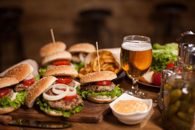 Beste happy hour burger mit kaltem bier auf einem holztisch im restaurant. pommes frites. grüner salat.