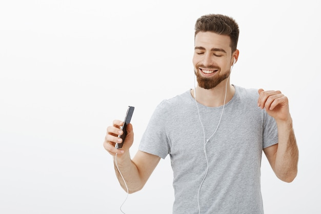Beste musik-app aller zeiten. freudiger charismatischer sorgloser gutaussehender mann mit bart und kranken augenbrauen, die augen vor freude und freude schließen, breit lächelnd smartphone halten, lieder in kopfhörern hörend, tanzend