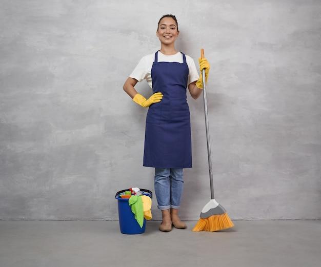 Beste reinigungsdienste. fröhliche junge putzfrau in uniform und gummihandschuhen, die besen und eimer mit verschiedenen reinigungsprodukten hält, in die kamera schaut und lächelt, gegen graue wand stehend