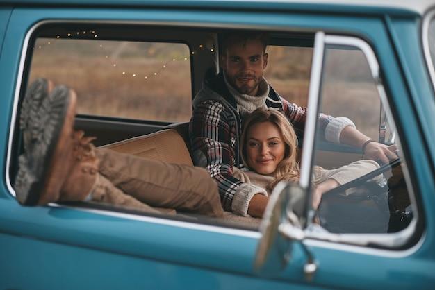 Beste reise aller zeiten. attraktive junge frau, die sich ausruht und lächelt, während ihr freund mini-van im retro-stil fährt